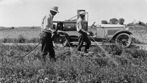P2011-22_17, 2 men spraying sodium chlorate onto weeds by side of road, car with equipment behind, ca 1936